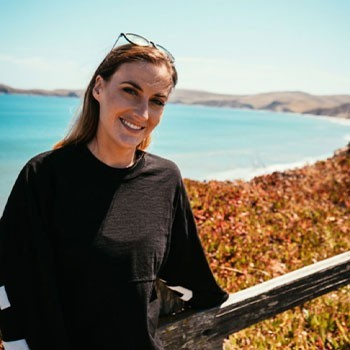 Casey, Ads Team Director at Elevate Her Marketing, smiles at the camera in front of the ocean