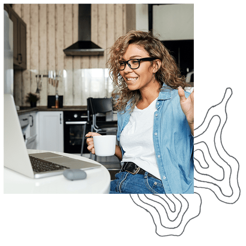 Woman smiles at her computer while drinking coffee