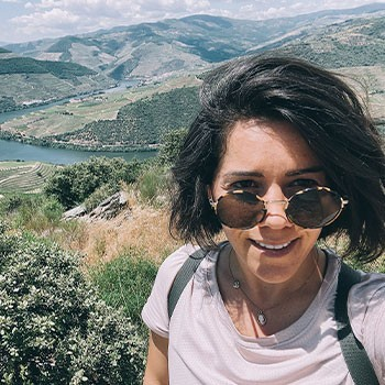 Frannie, Owner of Elevate Her Marketing, smiles at the camera wearing sunglasses with mountains in the background