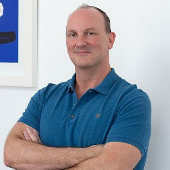 Geoffrey, Operations Manager at Elevate Her Marketing, folds his arms and smiles in front of a white wall